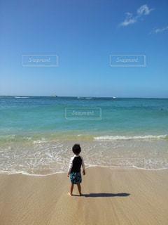 海の横にある浜辺を横切って歩いている人々のグループの写真・画像素材[2132232]