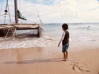 浜辺の砂の中に立っている小さな男の子の写真・画像素材[2132235]