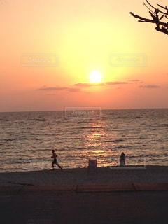 海に隣接する浜辺の夕日とランニングの写真・画像素材[2114007]