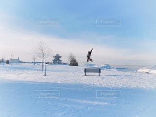 雪に覆われた場所で元気に男性がジャンプしている後姿の写真・画像素材[2129941]