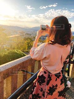 フェンスの隣に立っている人の写真・画像素材[2283192]