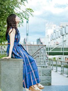 建物の前に立つ青いドレスを着た女性の写真・画像素材[2378379]