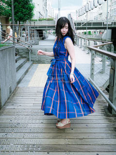フェンスの隣に立っている小さな女の子の写真・画像素材[2378381]