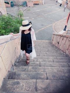 レンガの壁の隣の歩道を歩いている人の写真・画像素材[2378385]