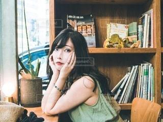 本棚の前に座っている女性の写真・画像素材[3437229]