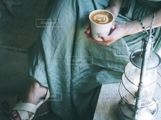 コーヒーを飲みながらテーブルに座っている人の写真・画像素材[3855848]