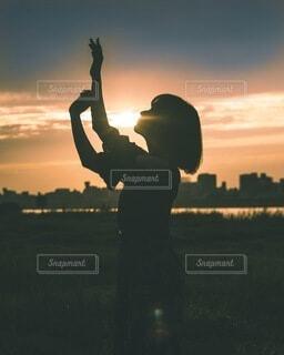 夕日の前に立っている人の写真・画像素材[4093798]