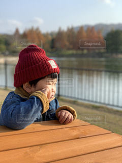 ベンチに赤い帽子をかぶった小さな男の子の写真・画像素材[2414900]