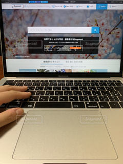 テーブルの上に座っている開いているラップトップコンピュータのスクリーンショットの写真・画像素材[2330998]