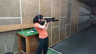 オレンジ色のTシャツを着て射撃する女性の写真・画像素材[2162922]