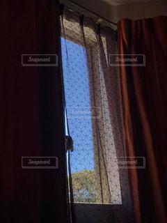 カーテン越しに見る青空の写真・画像素材[2167621]