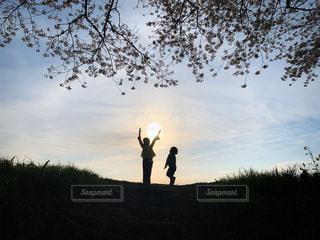 子ども,家族,2人,風景,空,夕日,桜,太陽,シルエット,光,河原,夕陽