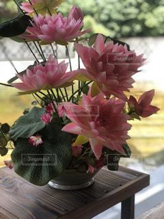 テーブルの上にピンクの花を詰めた花瓶の写真・画像素材[2141564]