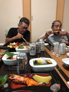 食卓に座って食べ物を食べる人々のグループの写真・画像素材[2177761]