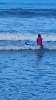 水の体の上に波に乗っている男の写真・画像素材[2329184]