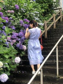 レンガの壁の隣に立っている若い女の子の写真・画像素材[2377251]