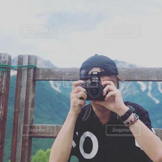 鏡の前に立つ人がカメラに向かってポーズをとるの写真・画像素材[2432395]
