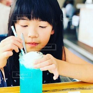 食べ物を食べるテーブルに座っている女性の写真・画像素材[3501653]