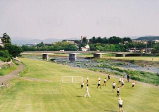 河川敷でサッカーをする小学生と教師 - No.705980