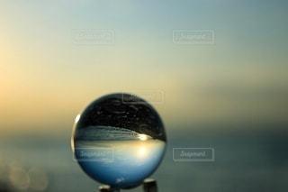 ガラス玉に映る朝陽と海の写真・画像素材[3391721]