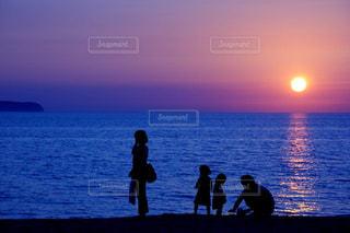 水の体の上に日没の前の人々のグループの写真・画像素材[2336730]