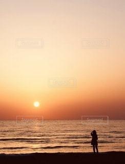 夕日の前のビーチに立っている人の写真・画像素材[3409257]