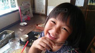 食べ物を食べながらテーブルに座っている小さな女の子の写真・画像素材[2298720]