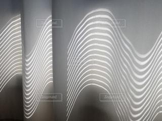 ブラインドの影が映るカーテンの写真・画像素材[2164818]
