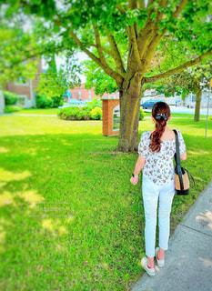 白コーデで木の下に立つ女性の写真・画像素材[2316915]