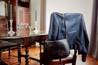 ダイニングルームの椅子に掛かってるジャケットとバッグの写真・画像素材[2646144]