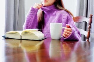 ニットを着て自宅でコーヒーを飲みながら読書をする女性の写真・画像素材[2693202]