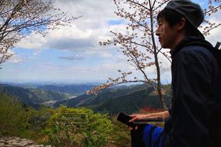 山の前に立っている男の写真・画像素材[2214420]