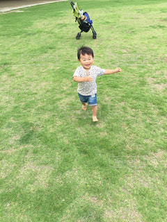 草の上に立っている小さな男の子の写真・画像素材[2117138]