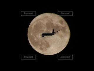 満月に飛行機のシルエットの写真・画像素材[4857640]