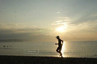 夕陽に向かって走る男の写真・画像素材[2108412]