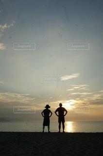 背景に夕日がある浜辺に立っている人々のグループの写真・画像素材[2132415]