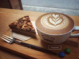 木製のテーブルの上に座っているコーヒー1杯の写真・画像素材[2123230]