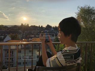 空,建物,夏,木,太陽,ベランダ,景色,スマホ,子供,人物,人,座る,旅行,写真,朝,スイス,ホテル,中学生,夏休み,日の出,家族旅行,半袖