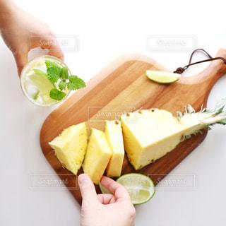グラスとパイナップルを持っている手の写真・画像素材[1824685]