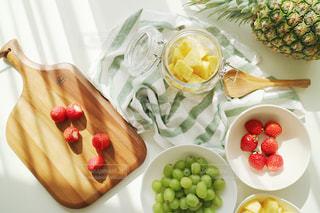 テーブルにフルーツとガラス容器の写真・画像素材[1828001]