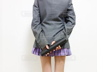ブレザーの制服を着た女子の後ろ姿、両手に卒業証書を持っている写真の写真・画像素材[1133404]