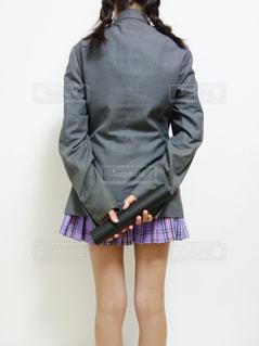 ブレザーの制服を着た女子の後ろ姿、両手に卒業証書を両手で持っているの写真・画像素材[1133412]
