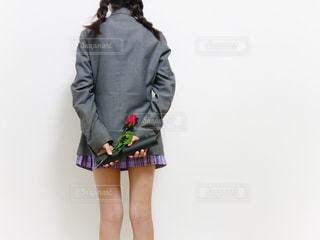 ブレザーの制服を着た女子の後ろ姿、両手に卒業証書と一輪の薔薇を持っているの写真・画像素材[1133437]
