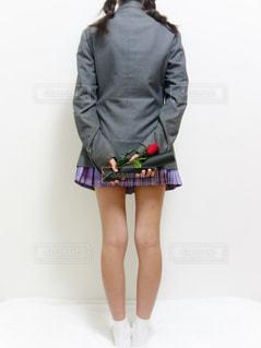 ブレザーの制服を着た女子の後ろ姿、両手に卒業証書と一輪の薔薇を持っています。の写真・画像素材[1133447]