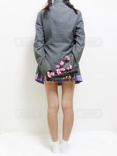 ブレザーの制服を着た女子高生の後ろ姿、両手に卒業証書と桜を持っているの写真・画像素材[1133483]
