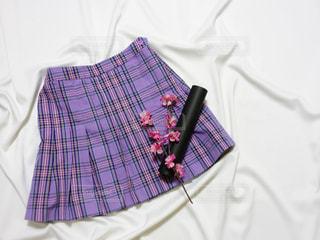 紫の制服ミニスカートと卒業証書用丸筒と桜の置き画写真の写真・画像素材[1133527]
