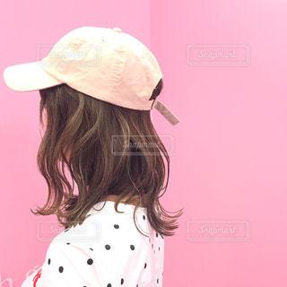 ピンクの背景にピンクの帽子をかぶったセミロングヘアの女性の横顔の写真・画像素材[1448403]