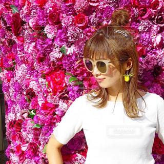 渋谷のピンクのお花のフォトスポットでサングラスを付けた女性の写真・画像素材[1489884]