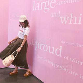 フォトジェニックなピンクの前に立っているカジュアルコーデの女性の写真・画像素材[1489898]