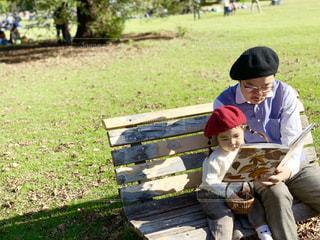 公園のベンチに座って読書をするパパと娘の写真・画像素材[1600976]